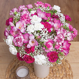 A charming display of hot pink Freesias beautifully complemented by a mixture of purple, white and pink Spray Carnations.<br /><br />