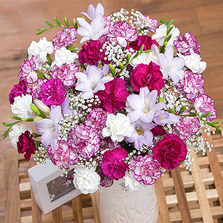 A charming arrangement of Freesias and Spray Carnations in shades of lavender, purple and white.