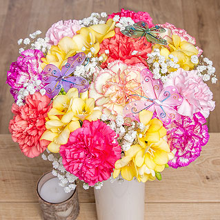 Carnations in mixed colours of cerise, orange, yellow and pink are joined by pretty yellow Freesia.<br /><br />Gentle white Gypsophila and three fun keepsake butterfly picks complete this charming arrangement.