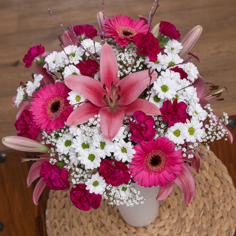 A delightful arrangement including pink Lilies, purple Spray Carnations and sparkling pink birch.