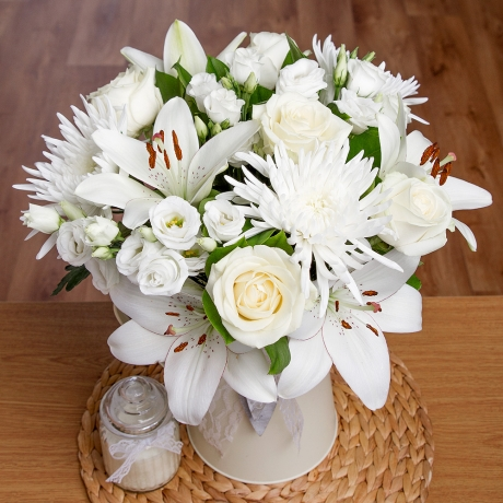 Stunning white Avalanche Roses are complemented by single white Anastasia, Asiatic Lilies and finished with Salal Leaves.<br /><br />A simple yet elegant display of striking white flowers.