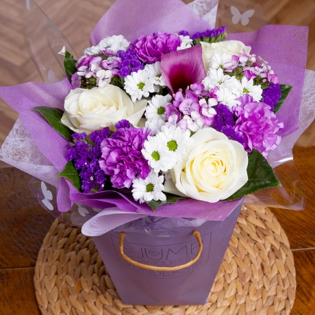 Gorgeous Avalanche Roses, purple Carnations and lavender Alstroemeria delivered in a purple gift bag.