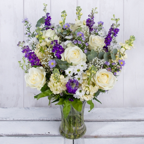 A stunning collection of white Avalanche Roses and white Snapdragon feature alongside lilac Aster and striking blue Delphinium.<br /><br />White Chrysanthemums and Eucalyptus leaves provide the perfect finish to this dreamy bouquet.