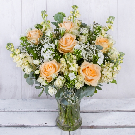 Eye-catching peach Roses are the focal point of this luxurious arrangement and are surrounded by white Snapdragon and dainty white Phlox.<br /><br />