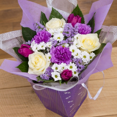 Avalanche Roses, Tulips and Carnations in purple and white delivered in a purple gift bag.