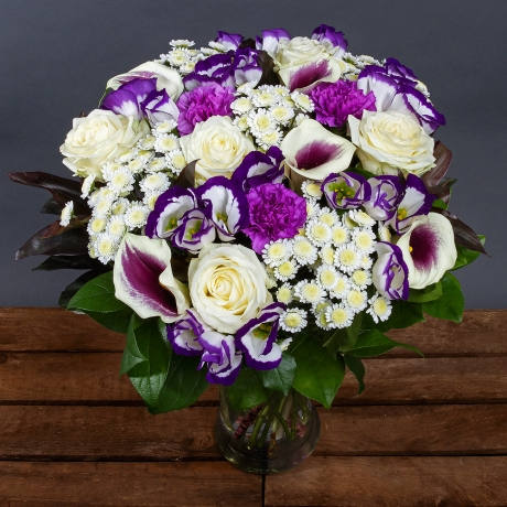 A selection of white Avalanche Roses and elegant purple-centred Calla Lilies feature alongside Moonlight Carnations and lavender Lisianthus.