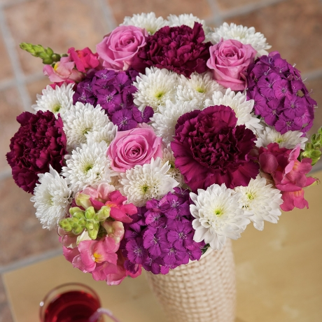 Gorgeous pink Aqua Roses and purple Sweet William are complemented by pink Antirrhinum and purple Carnations.<br /><br />White Euro Chrysanthemums provide a lovely finish to this charming bouquet which is rich in feminine hues.