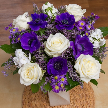 Exquisite cream Avalanche Roses are accompanied by stunning purple Anemones, lilac Aster & white Phlox.