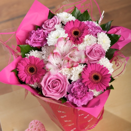 A gorgeous, ready-to-display arrangement of pink Alstroemeria and Aqua Roses in a pink gift bag.
