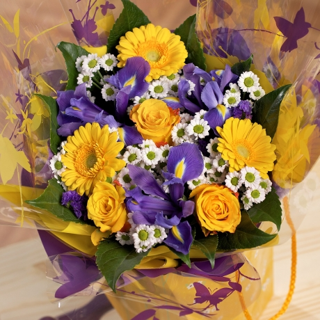 A beautiful ready-to-display arrangement of vibrant springtime blooms in a yellow daisy gift bag.
