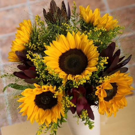 A truly show-stopping summer treat, our Sunflower Meadow bouquet is sure to spread a little summer sunshine.<br /><br />Five eye-catching Sunflowers are beautifully complemented by sunny yellow Solidago and pretty Panicum grass.<br /><br />Bold Leucadendron leaves provide the perfect finishing touch to this charming Sunflower bouquet.