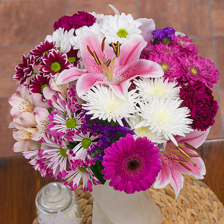 This gorgeous feminine bouquet in shades of light pink, purple and white is the perfect gift to brighten up a loved one's home this summer.<br /><br />Pink oriental lilies are surrounded by purple Germini, pink Alstroemeria, purple Carnations, white and purple Chrysanthemums and blue Statice.