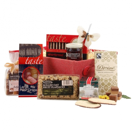 A delicious hamper piled high with tea time treats and presented in a smart red woven tray.