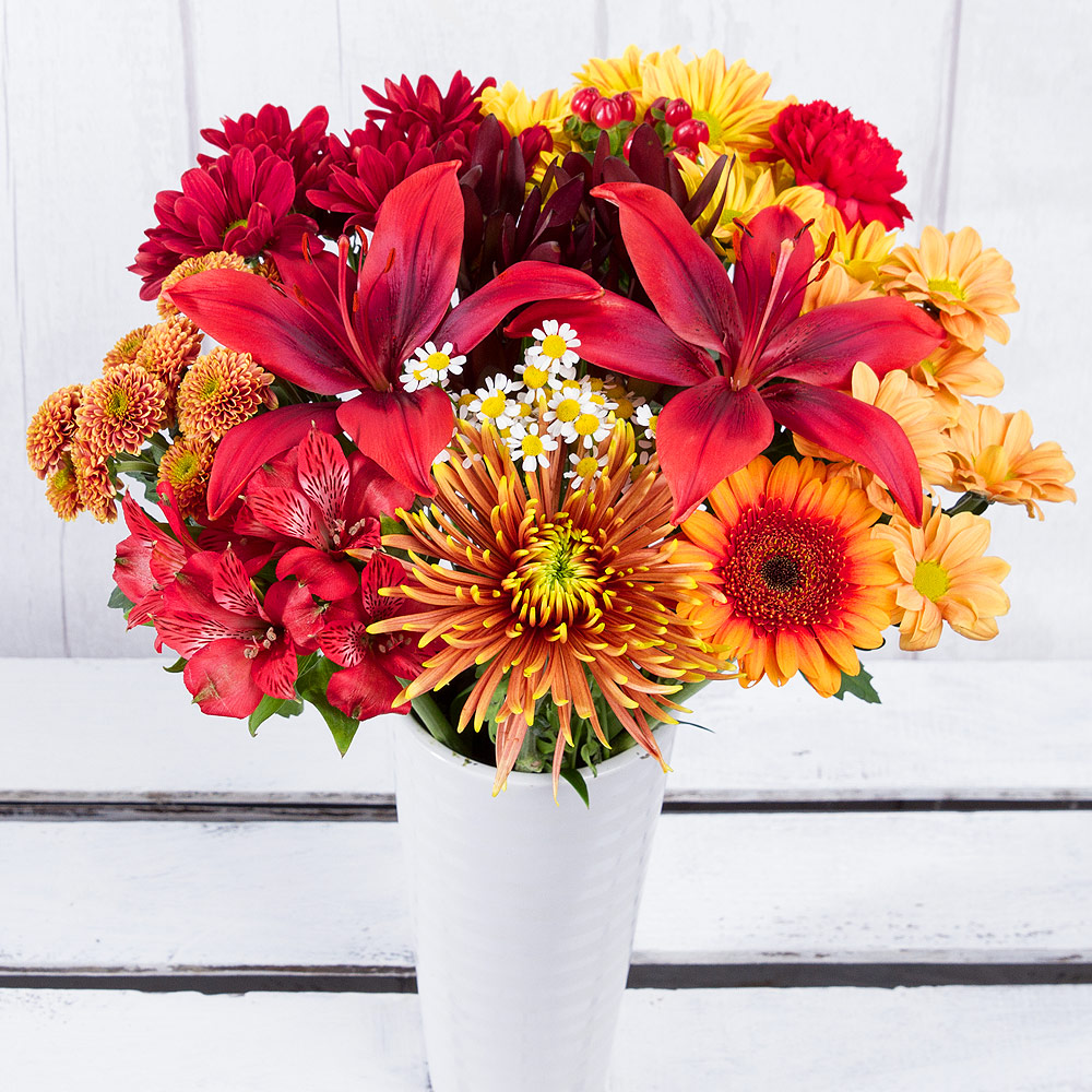 A unique and showy orange Leucadendron, stunning red Asiatic Lily and bright orange Germini are the focus of this autumn-themed bouquet.<br/><br/>Alstroemeria, Matricaria, Hypericum Berries and a selection of Chrysanthemums in autumn shades of yellow, orange and red make this the perfect seasonal display.