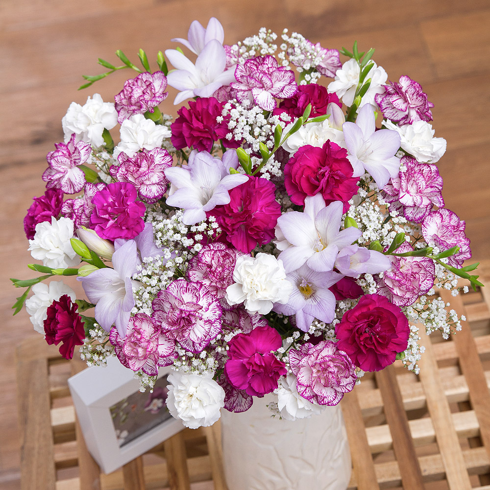 A charming arrangement of lilac Freesias beautifully complemented with a delightful mixture of purple, white and purple-edged Spray Carnations.<br /><br />Perfectly finished with white Gypsophila, this will make a wonderful gift for someone special.