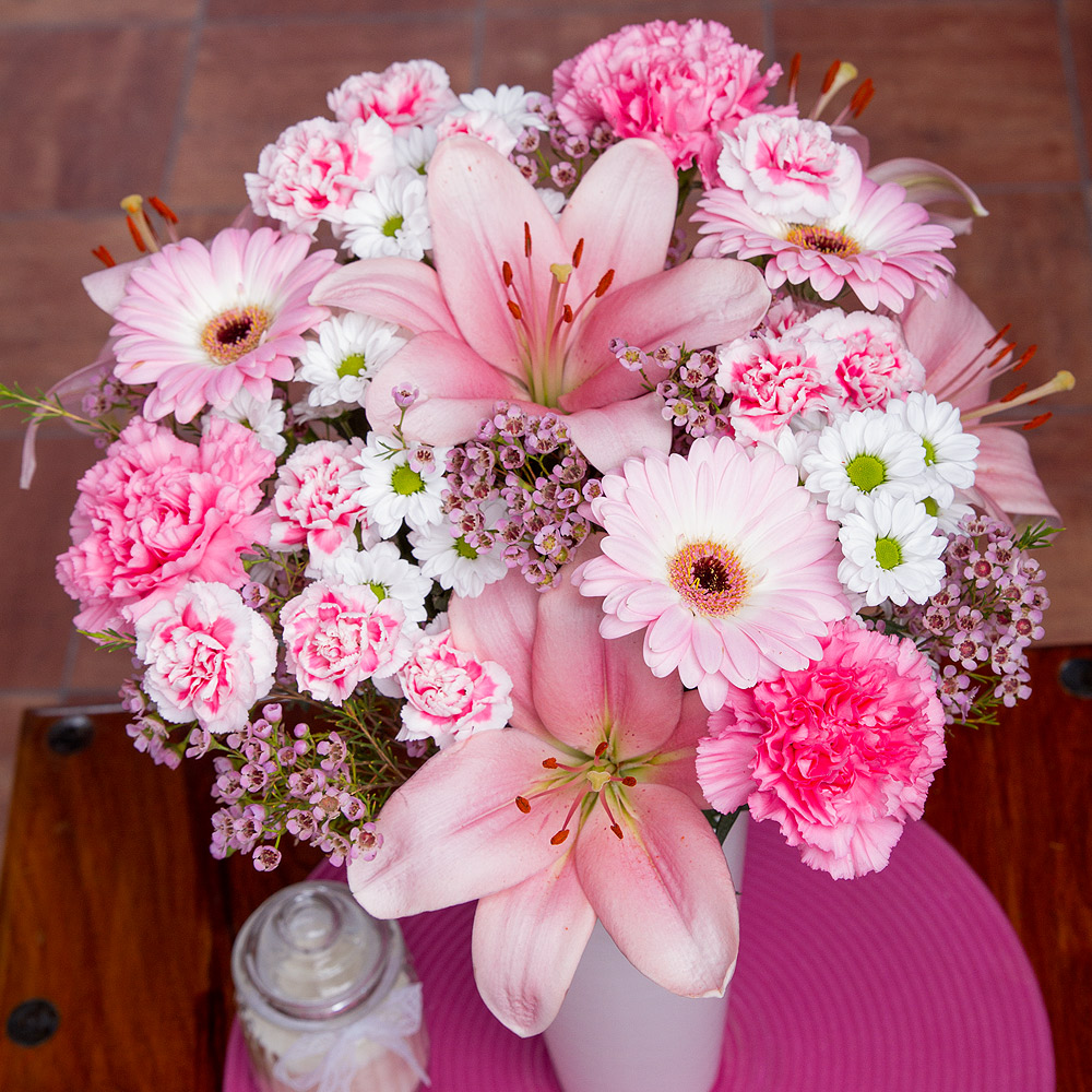 A beautiful arrangement of pale pink Lilies, Germini and Carnations alongside crisp white Chrysanthemums and perfectly finished with pink Wax Flower.
