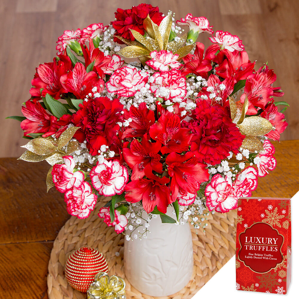 This festive display is created with bold red single Carnations and Burgundy Spray Carnations, gorgeous dark red Alstroemeria and delicate white Gypsophila. <br /><br />Festive gold glitter Ruscus leaf and a delicious 96g box of Belgian truffles make the gift extra special.