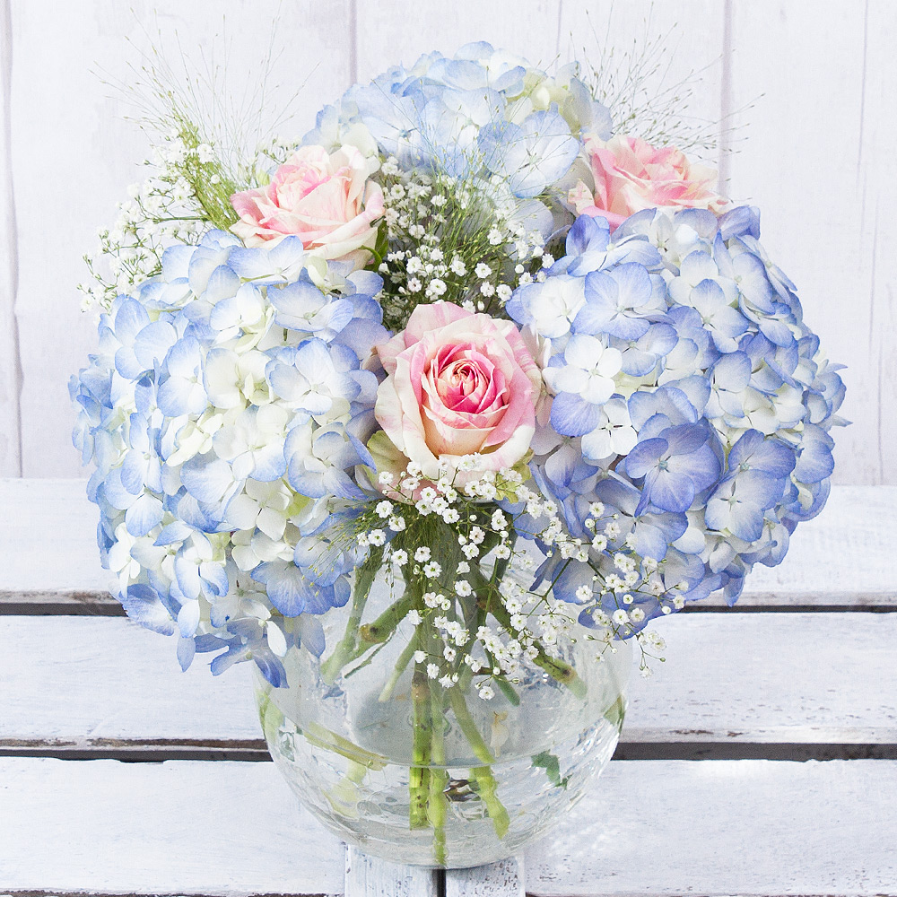 Beautiful pastel blue Hydrangeas are paired with pink and white Sweet Harlequin Roses to make a delightful summer bouquet.<br/><br/>Delicate white Gypsophila and soft Panicum grass provide the perfect finishing touch.