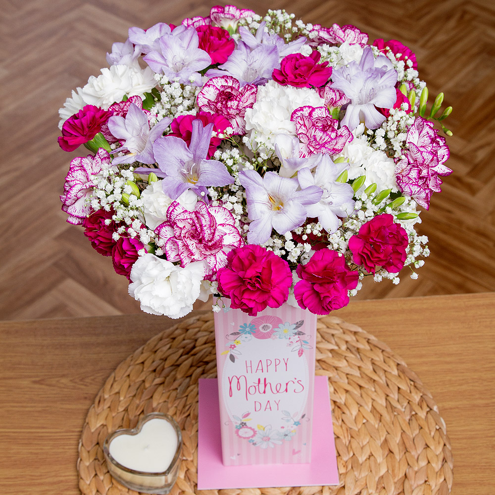 A delightful arrangement of lavender Freesias, mixed colour Spray Carnations and Gypsohila feature in this charming Mother's Day gift.<br /><br />A 'Happy Mother's Day' card vase accompanies the gift, making it the ideal surprise to send this Mother's Day.