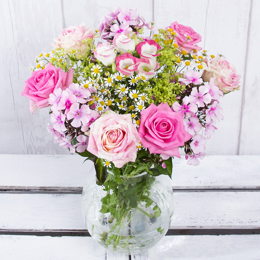 A show of gentle pink colour with Aqua Roses and two-tone Harlequin Roses joined by pretty Phlox and Lisianthus.<br/><br/>Matricaria Daisies and greenery combine to make this a wonderful gift to display in the home.