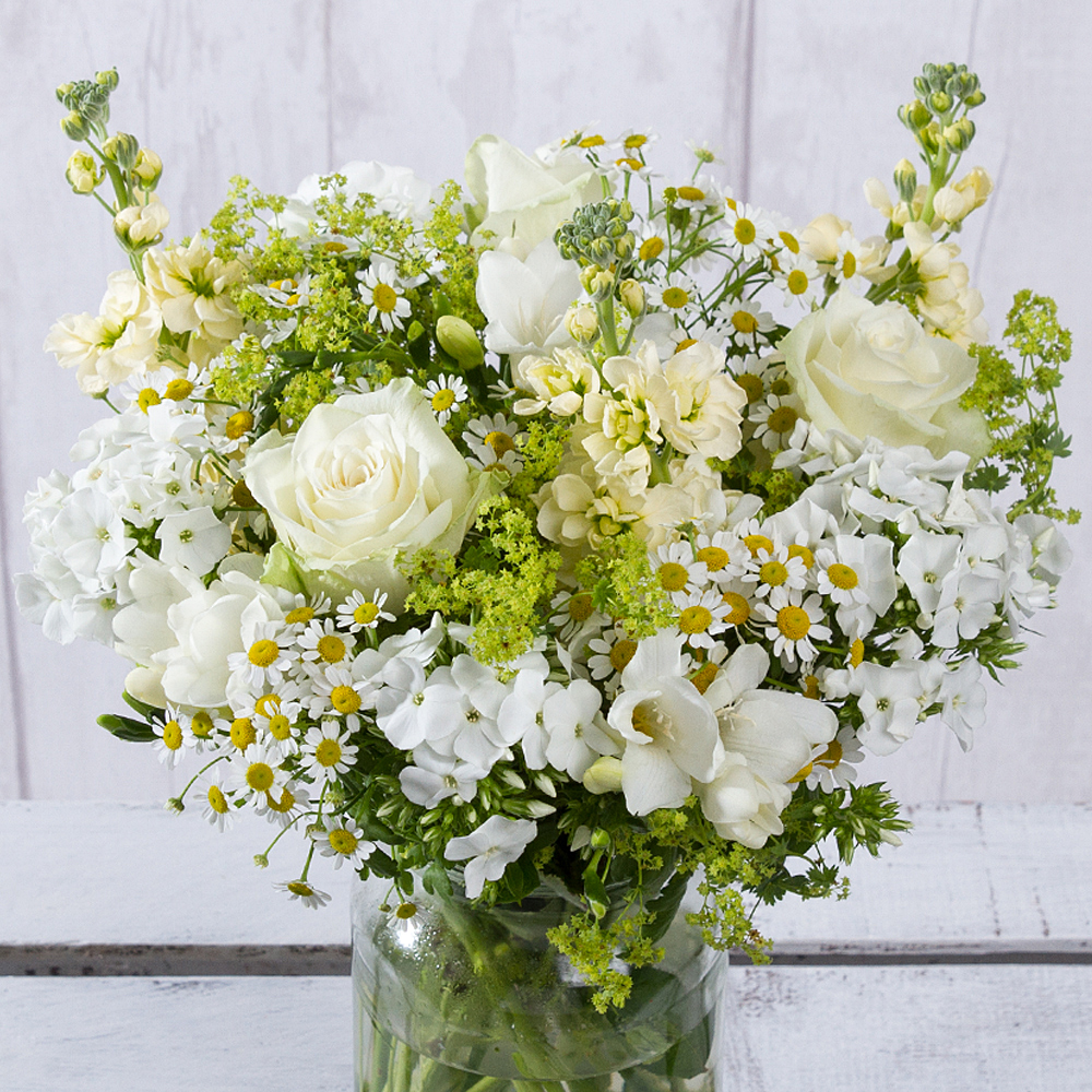 An array of wonderful white Roses, Phlox and Freesia are joined by cream Stocks and daisy-like Matricaria.<BR/><BR/>Alchemilla greenery provides a wonderful finish to this bubbly, summer display.