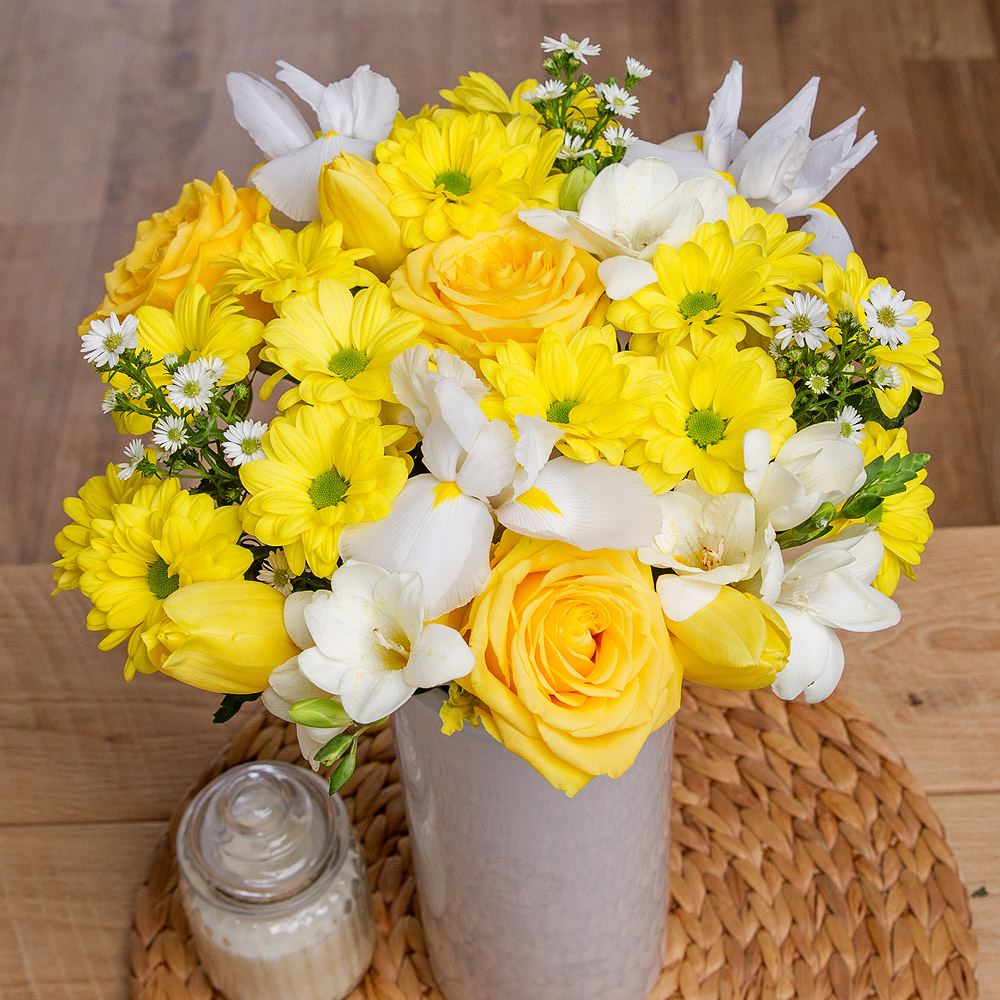 This eye-catching springtime arrangement features an array of fresh, seasonal blooms.<br /><br />Bright yellow Roses, Tulips and Chrysanthemums are beautifully complemented by pretty white Freesias and Iris.